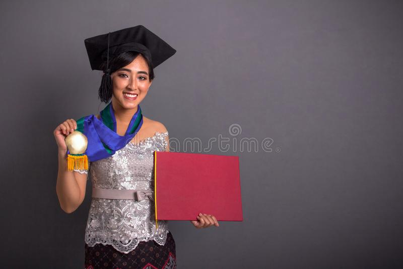 Menina bonita que mostra seus medalha e certificado da graduação imagens de stock