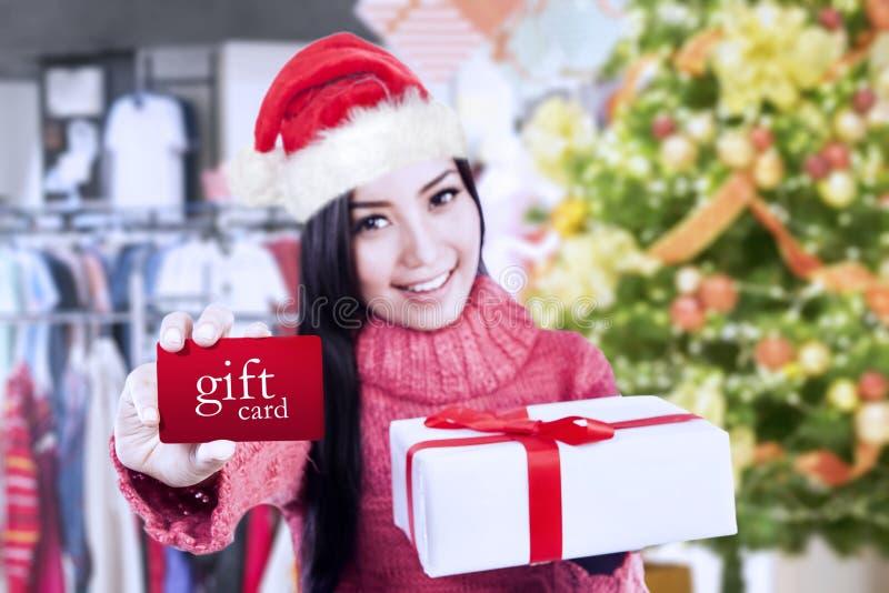 Menina bonita que mostra um vale-oferta e uma caixa foto de stock royalty free