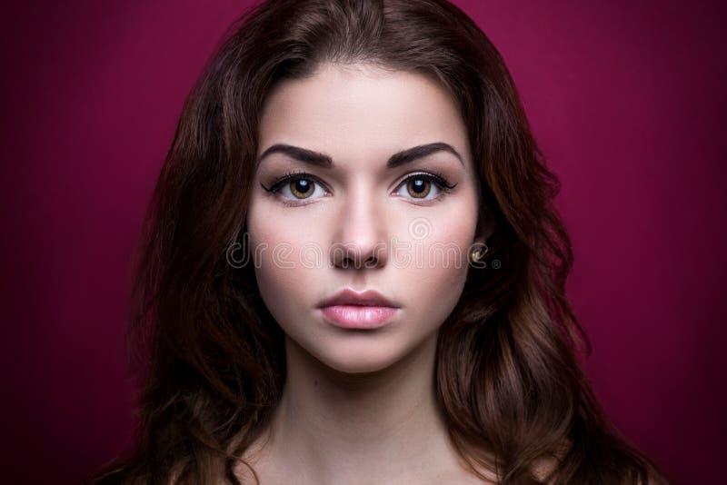 Menina bonita que olha a câmera tiro no estúdio Em um fundo cor-de-rosa Cara forte Olhos da íris Jovem mulher do retrato fotos de stock