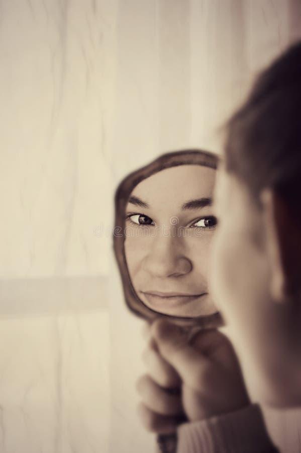 Menina bonita que olha no espelho imagem de stock