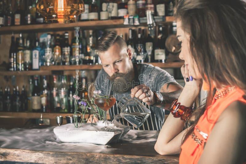 Menina bonita que olha o barman considerável foto de stock