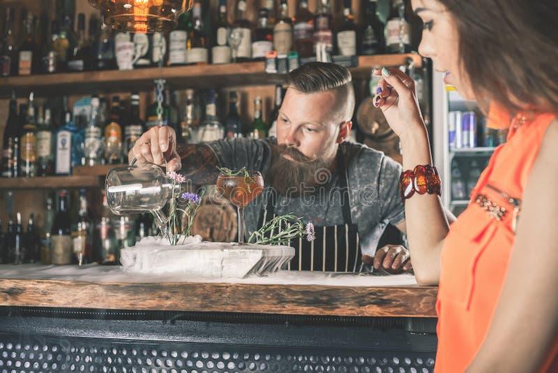 Menina bonita que olha o barman considerável fotos de stock