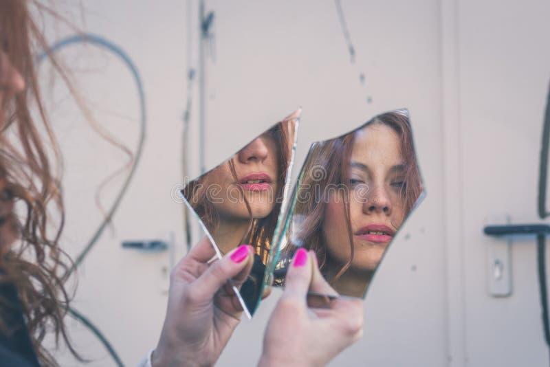 Menina bonita que olha si mesma em um espelho imagem de stock