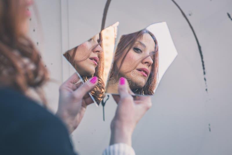 Menina bonita que olha si mesma em um espelho fotografia de stock royalty free
