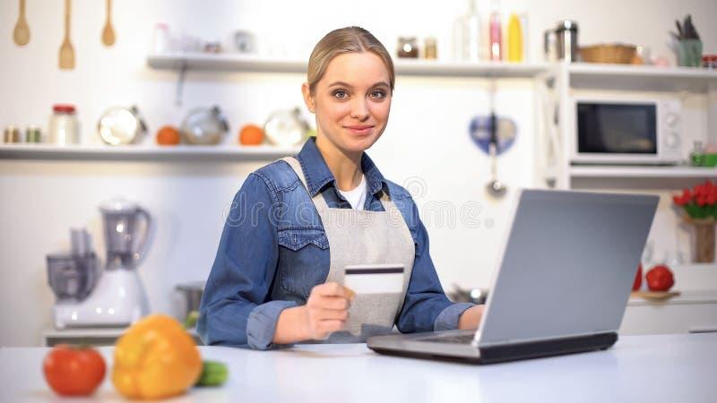 Menina bonita que paga pela compra do alimento sobre o Internet, serviço online conveniente imagem de stock