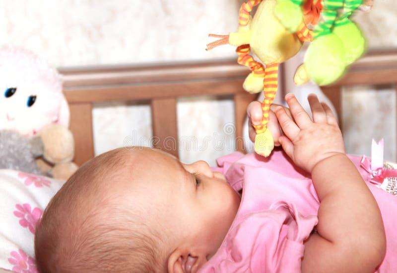 Menina bonita que prende o brinquedo colorido foto de stock royalty free