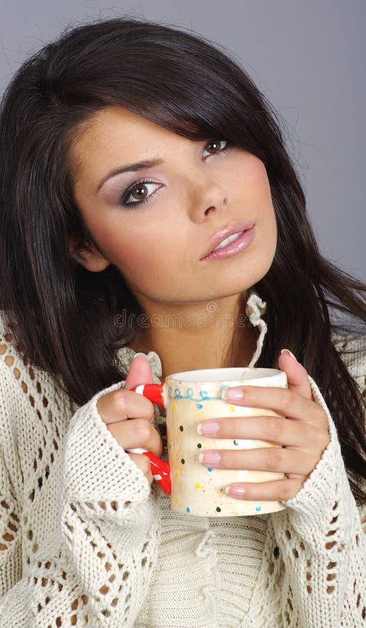 Menina bonita que prende o copo de chá quente fotografia de stock