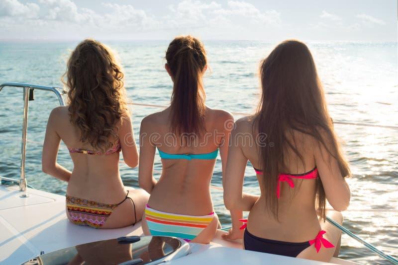 Menina bonita que relaxa em um iate Vela no mar imagem de stock