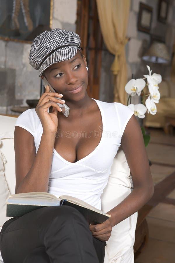 Menina bonita que relaxa em um sofá branco imagem de stock royalty free