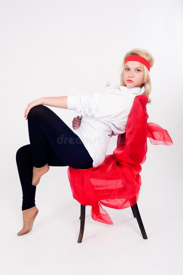 Menina bonita que relaxa na cadeira imagem de stock royalty free