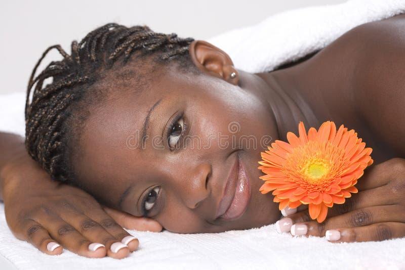 Menina bonita que relaxa na tabela da massagem imagens de stock royalty free