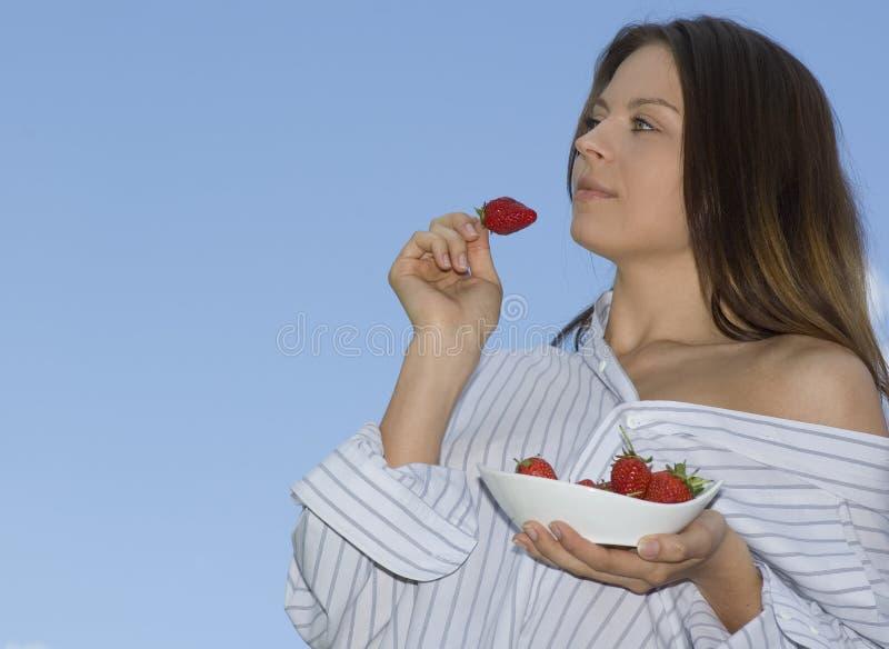A menina bonita que relaxa no balcão e come fresco vermelho fotografia de stock royalty free