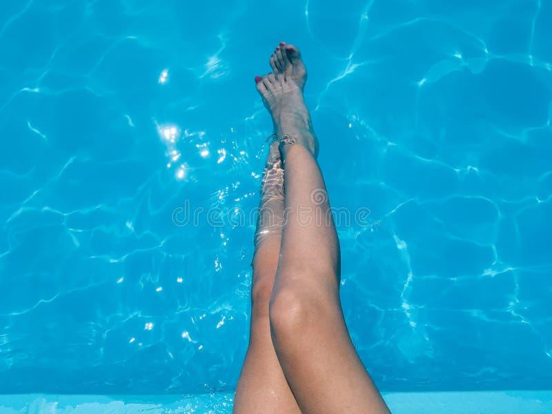 Menina bonita que relaxa seus pés na água da associação imagem de stock