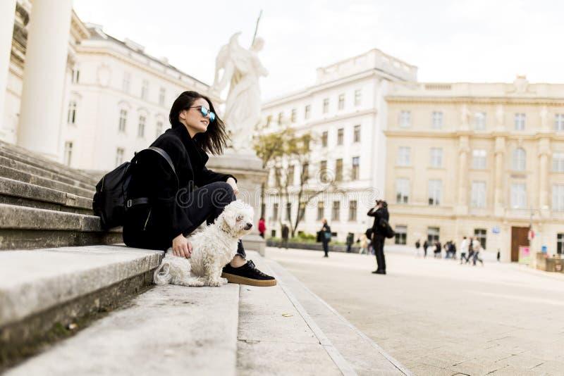 Menina bonita que senta-se em escadas com seu cão de estimação fotografia de stock