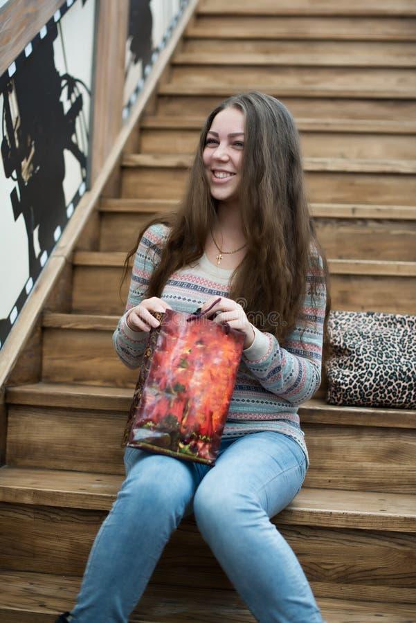 Menina bonita que senta-se em escadas de madeira imagem de stock royalty free