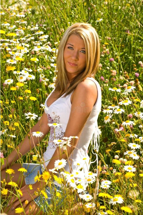 Menina bonita que senta-se em flores do campo fotografia de stock royalty free