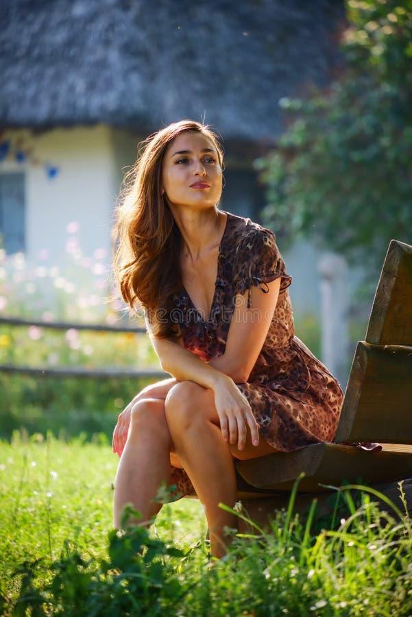 Menina bonita que senta-se em um banco imagens de stock