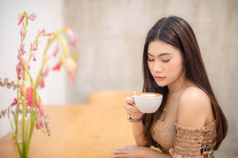 Menina bonita que senta-se em um caf? fotos de stock