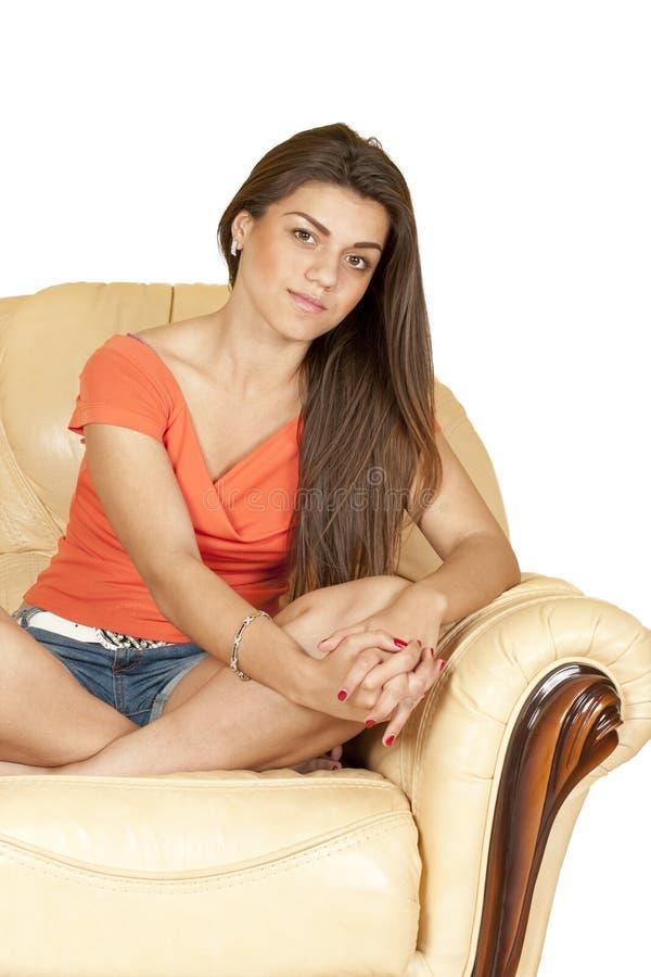 Menina bonita que senta-se em um sofá amarelo da pele foto de stock