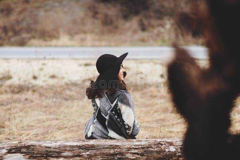 Menina bonita que senta-se em uma placa de madeira As mulheres sentem felizes com natureza fotos de stock royalty free