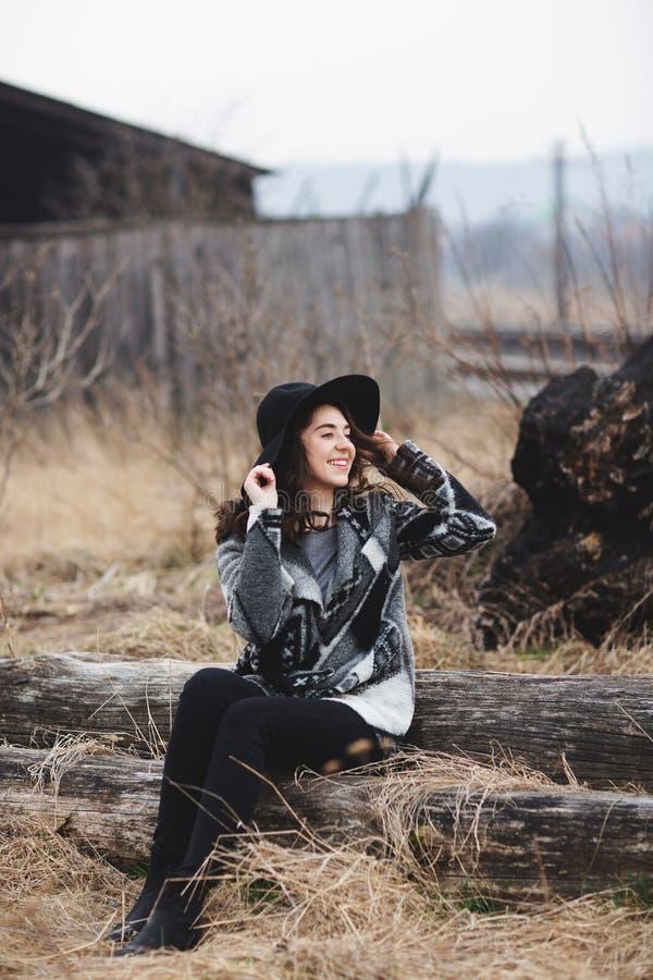 Menina bonita que senta-se em uma placa de madeira As mulheres sentem felizes com natureza imagem de stock royalty free
