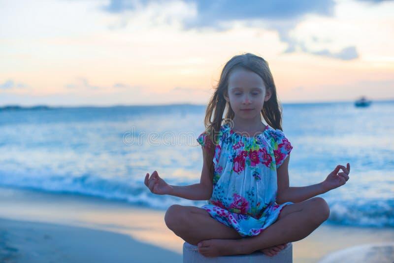 Menina bonita que senta-se em uma posição de lótus fotografia de stock royalty free