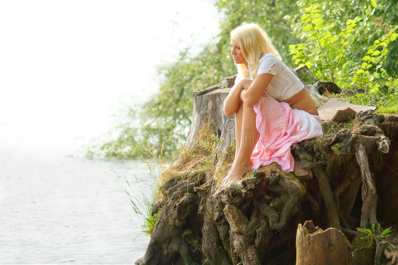 Menina Bonita Que Senta-se Na Costa E Que Olha Afastado Imagem de Stock