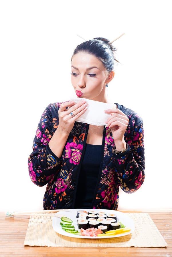 A menina bonita que senta-se na tabela e limpa sua cara com uma toalha ou um guardanapo Mentiras próximas uma placa do sushi, iso foto de stock