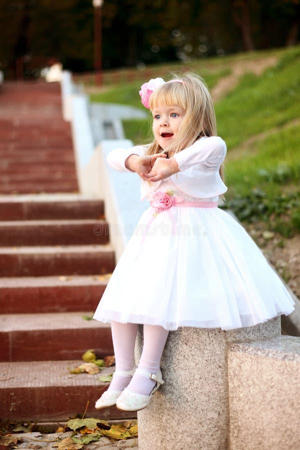 Menina bonita que senta-se nas escadas imagens de stock royalty free