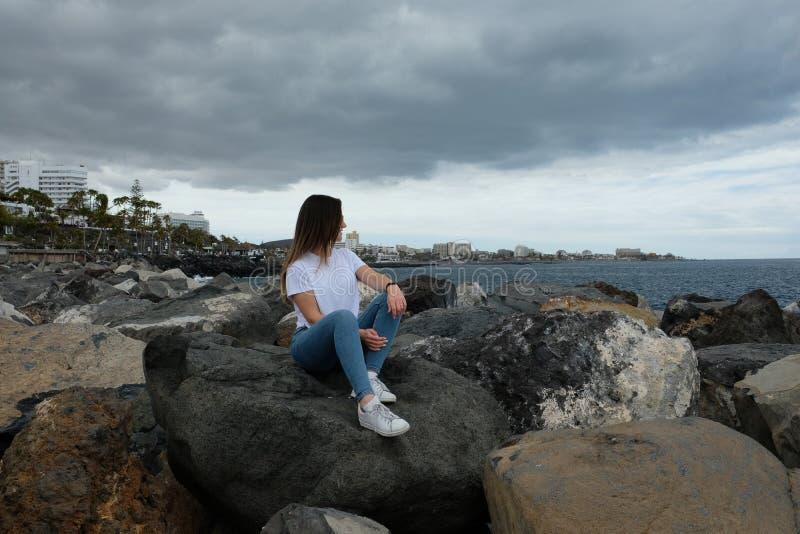Menina bonita que senta-se nas rochas da praia que olham ao mar fotos de stock royalty free