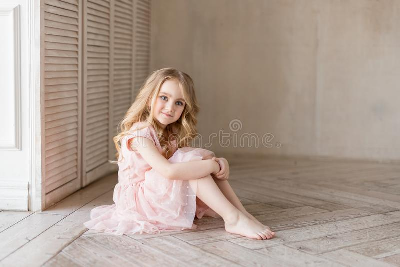 Menina bonita bonita que senta-se no assoalho e no sorriso Foto interna Menina agradável imagens de stock royalty free