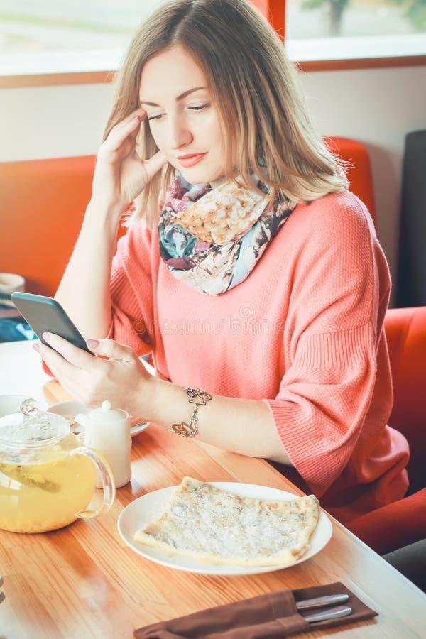Menina bonita que senta-se no café que guarda um smartphone Hora para o co fotos de stock royalty free