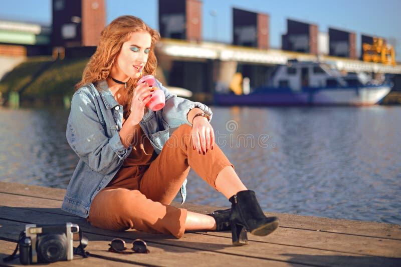 Menina bonita que senta-se no cais perto do rio Modelo do moderno na gargantilha com cerly cabelo louro A menina na bebida quente imagens de stock
