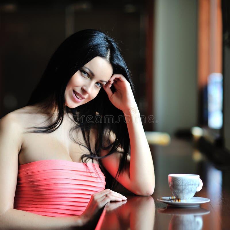 Menina bonita que senta-se no restaurante com um copo do chá ou do co foto de stock