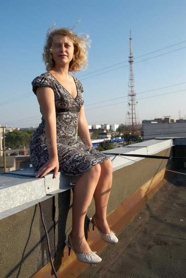 Menina bonita que senta-se no telhado imagens de stock royalty free