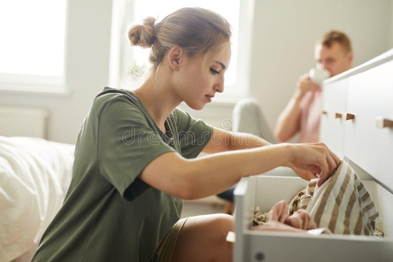 Menina bonita que senta-se pela gaveta aberta ao procurar para a roupa nova fotografia de stock