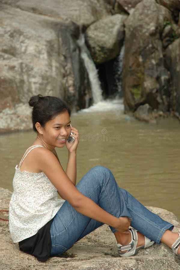 Menina bonita que sorri ao falar no telefone móvel imagens de stock royalty free