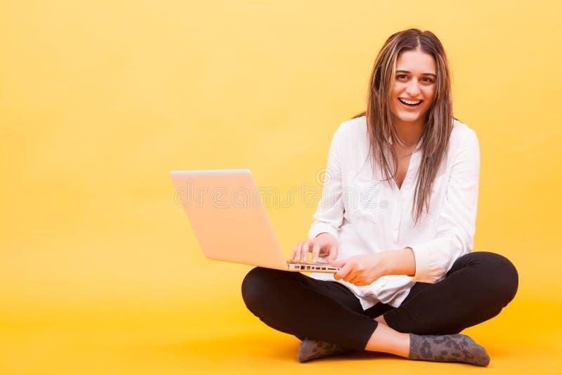 Menina bonita que sorri ao guardar seu portátil e ao sentar-se para baixo sobre o fundo amarelo imagens de stock royalty free