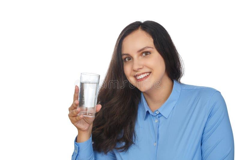 Menina bonita que sorri ao guardar um vidro da água imagem de stock