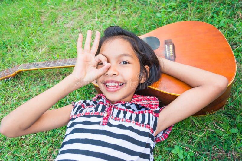 Menina bonita que sorri com a guitarra, encontrando-se para baixo na grama imagens de stock