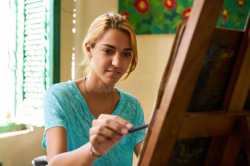 Menina bonita que sorri e que pinta em Art School imagem de stock royalty free
