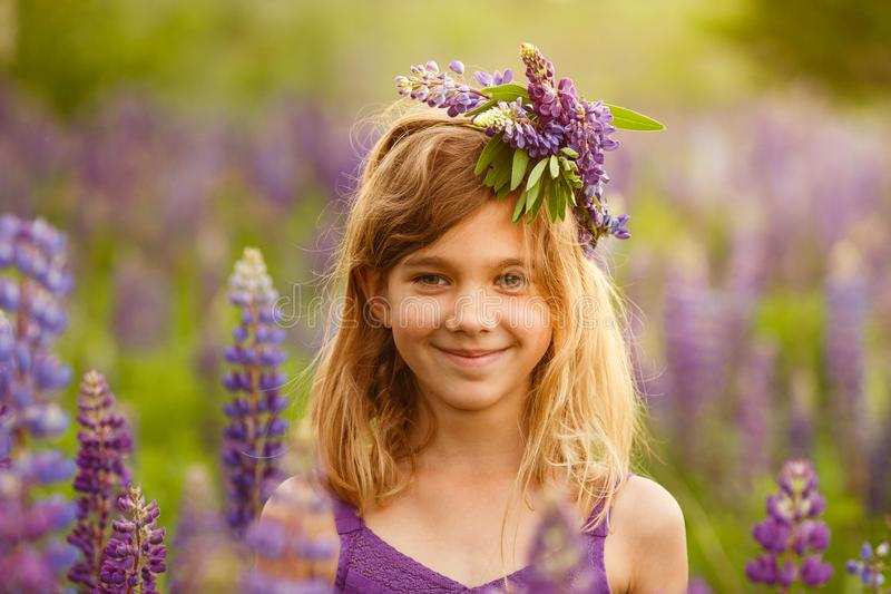 Menina bonita que sorri em um vestido violeta com uma grinalda dos lupines imagem de stock