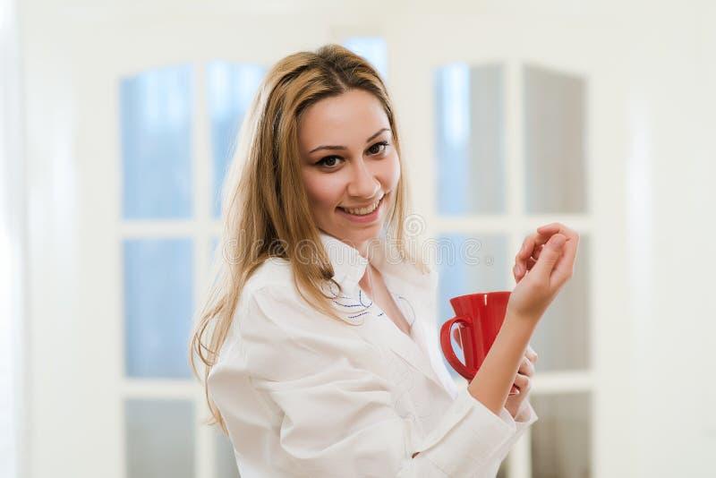 Menina bonita que sorri guardando uma xícara de café foto de stock royalty free