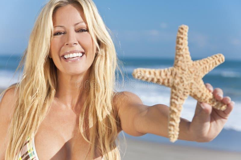 Menina bonita que sorri na praia com Starfish foto de stock royalty free
