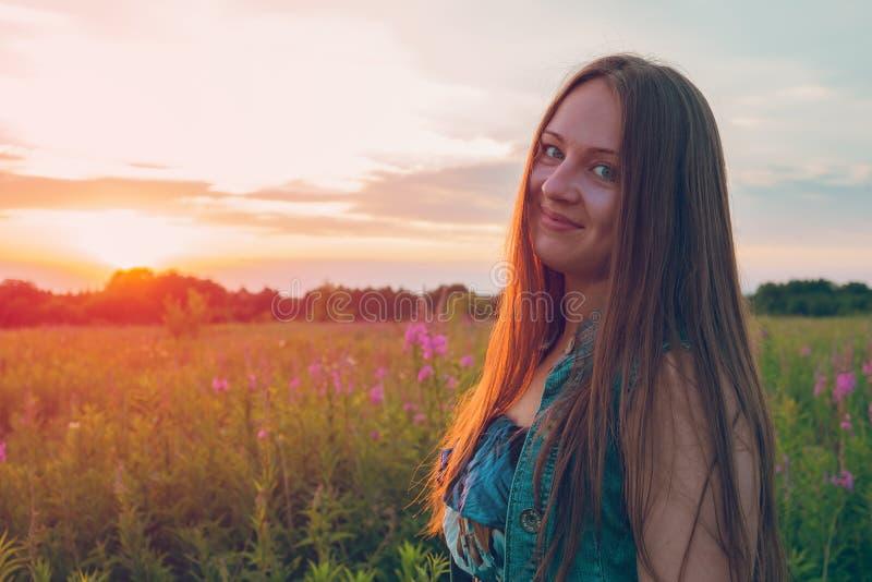 Menina bonita que sorri no campo do por do sol imagens de stock