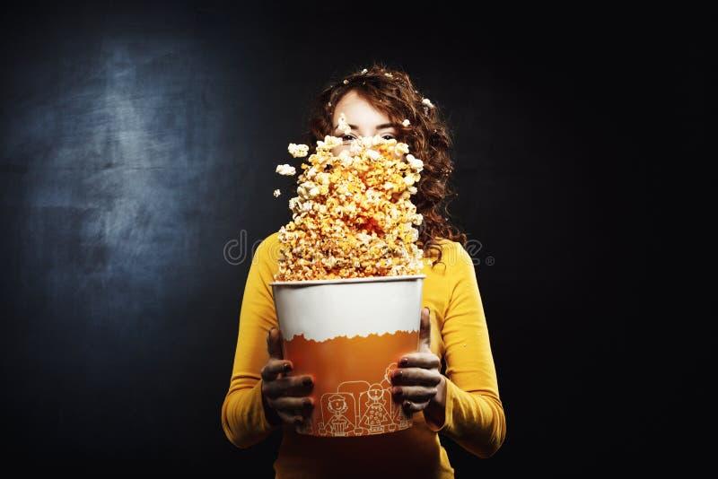 Menina bonita que tem o divertimento no teatro de filme que agita a cubeta da pipoca fotografia de stock