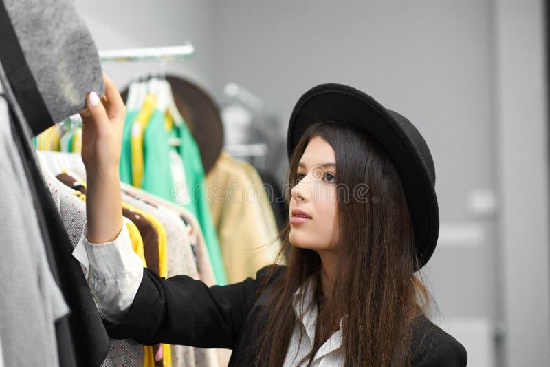 Menina bonita que tenta em chapéus negros na loja da roupa imagem de stock royalty free