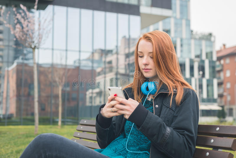 Menina bonita que texting em um banco foto de stock