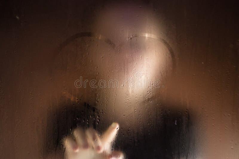 Menina bonita que toca na pintura molhada da janela e de dedo no vidro dos pingos de chuva imagens de stock