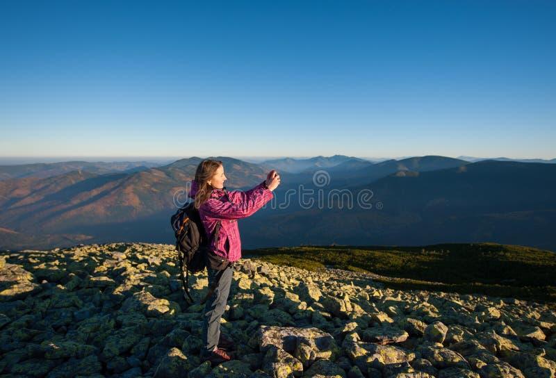 Menina bonita que toma a imagem com seu smartphone nas montanhas foto de stock